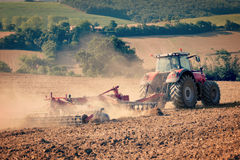 Tractor and stubble plough in an harvested field Stock Photography