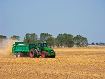 Tractor in summer field during harvest Stock Photos