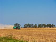 Tractor in summer field during harvest Royalty Free Stock Image