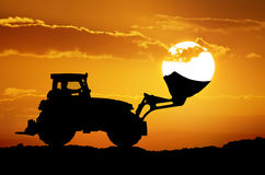 Tractor and sun into shovel bucket. Royalty Free Stock Image