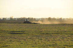 Tractor at sunset plow plow a field. Tilling the soil in the fall after harvest. The end of the season Stock Photos