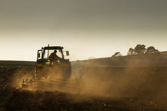 Tractor in sunset plowing the field Stock Images