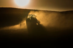 Tractor in sunset plowing the field Royalty Free Stock Photo