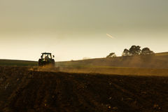Tractor in sunset plowing the field Royalty Free Stock Images