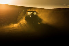 Tractor in sunset plowing the field Royalty Free Stock Photos