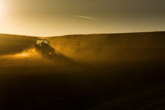 Tractor in sunset plowing the field Stock Photography