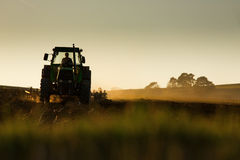 Tractor in sunset plowing the field Stock Image