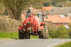 A tractor and tanker on road with houses Stock Photo