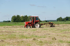 Tractor ted hay dry grass in agriculture field Stock Photography