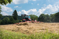 Tractor with tedder turning hay on the meadow Stock Photos