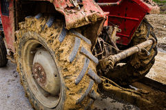 Tractor Tires With Mud. Detail of a tractor with diversity of visible mechanical parts and tires covered with mud on the side of a road Royalty Free Stock Image