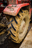 Tractor Tires With Mud. Detail of a tractor with diversity of visible mechanical parts and tires covered with mud on the side of a road Royalty Free Stock Photos