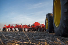 Tractor tires and seeding drill. Tractors tires and seeding drill parked on a field Stock Photo