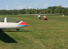 Tractor Towing Glider. MANOTICK, CANADA – AUGUST 19: A glider being towed on a grass airstrip after a flight at Rideau Valley Soaring on August 19, 2012 royalty free stock photo