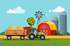 Tractor towing hay bales loaded to a trailer Stock Photo