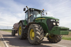 Tractor towing a trailer tank with fertilizers Royalty Free Stock Images