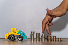 Tractor toy downloading a coins stack, hand as finger running on heap of coins Royalty Free Stock Image