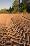 Tractor tracks in freshly plowed soil field sunny day Royalty Free Stock Images