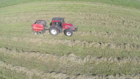 Bale hay. A tractor with a trailer, a baler, produces bales of hay stock video