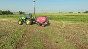 Hay bale. A tractor with a trailer, a baler, produces bales of hay stock video