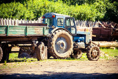 Tractor with trailer. Tractor blue assistant machinery farm transportation cargo Silos village Stock Photo