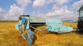 Tractor With Trailer Collecting Straw In Stubble stock footage