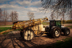 Tractor with trailer fertilizer-sprayer on country road Royalty Free Stock Image