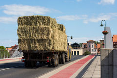 A tractor with trailer loaded with hay briquettes Stock Photo