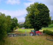 Tractor and trailer, in pastel country landscape setting. Royalty Free Stock Image