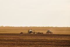 A tractor with a trailer plowing field for sowing of agricultural machinery is preparing for a new crop. Stock Photos