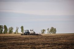 A tractor with a trailer plowing field for sowing of agricultural machinery is preparing for a new crop. Stock Image