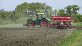Tractor with trailer seeder sowing cultivated field. Agricultural machinery stock video