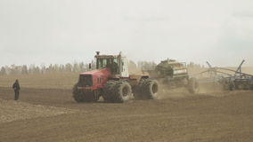 Tractor with trailer storage for grain and seed drill working in field. stock footage