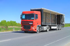 A Tractor Trailer Truck with an open trailer awnin. G on the road out of town. Sunny Royalty Free Stock Photos