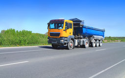 A Tractor Trailer Truck with tipper semi-trailer o. N the road out of town. April, sunny Royalty Free Stock Images
