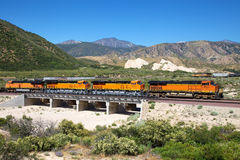 Tractor train passing through the bridge. Four tractor train traverse the tree made of concrete Stock Photo