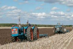 Tractor triplicado gama de dos vintages que tira de un arado fotos de archivo libres de regalías