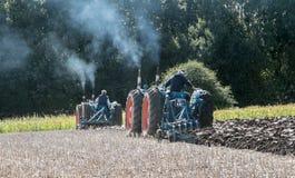 Tractor triplicado gama de dos vintages que tira de un arado fotografía de archivo libre de regalías