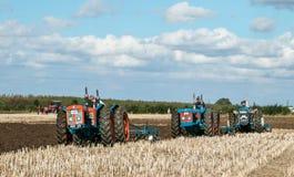 Tractor triplicado gama de tres vintages que tira de un arado fotos de archivo libres de regalías