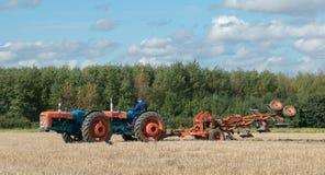 Tractor triplicado gama del vintage que tira de un arado imagenes de archivo