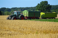 Tractor with two trailers at harvest on a wheat field Royalty Free Stock Images