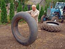 Tractor tyre repairing. Senior farmer repairing his tractor big tyre Royalty Free Stock Image