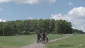 Tractor uitgespreide meststof op gecultiveerd gebied dichtbij bos stock video