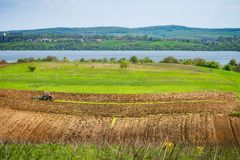 Tractor in a ukrainian field. Tractor fertilize a spring field before the seeding. Ukraine, Europe Royalty Free Stock Photography