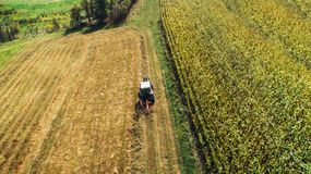 Tractor using rotary rakes machinery, harvesting details. Hay collecting and wheat production royalty free stock photo