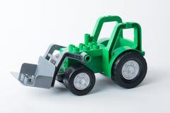 Tractor verde con el cubo gris en un fondo blanco Imagenes de archivo