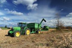 Tractor verde en el campo de granja Fotos de archivo