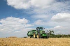 Tractor verde moderno que tira de un remolque en campo de la cosecha Fotografía de archivo