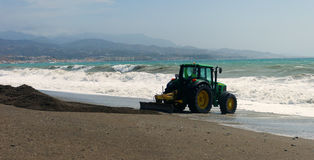 A tractor races to stem the tide. Stock Image