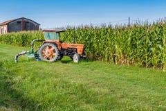 Tractor viejo delante de un campo de trigo Fotografía de archivo libre de regalías